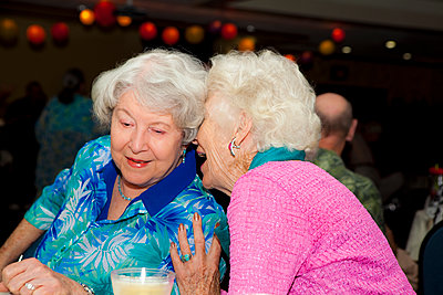 Older Caucasian women whispering at party in retirement home - p555m1408806 by Shestock