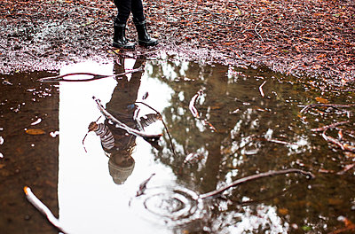 Reflection in puddle of Caucasian girl holding sticks - p555m1482047 by Adam Hester