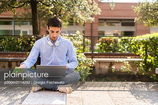 Young man using laptop, headphones around neck in the city - p300m2114292 von Giorgio Fochesato