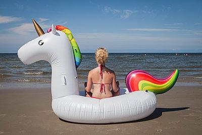 Frau meditiert auf Einhorn am Strand - p045m1590312 von Jasmin Sander