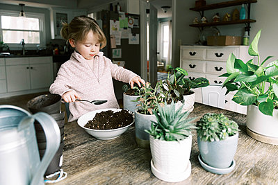 Toddler girl helping with re-potting plants and propagation. - p1166m2152344 by Cavan Images