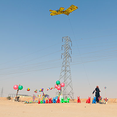 Souvenir salesman in the desert flying a kite - p1542m2142332 by Roger Grasas