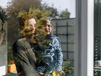 Father carrying son at the window at home - p300m2167233 by Kniel Synnatzschke