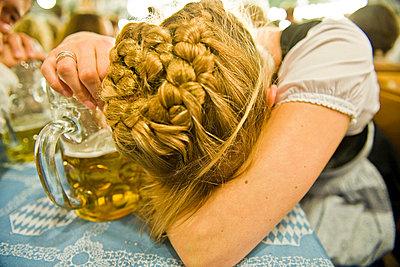 Erschöpfte Frau mit Maßkrug auf dem Oktoberfest in München, Bayern, Deutschland - p473m670366f by STOCK4B-RF