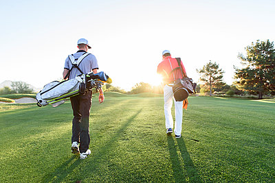 Men carrying golf bags on sunny golf course - p555m1472891 by Kolostock