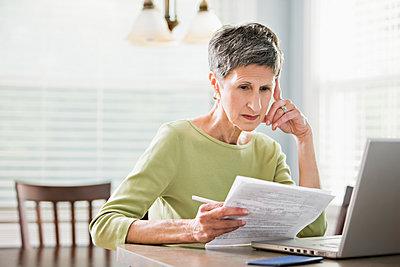 Senior woman paying bills on laptop - p555m1478464 by John Fedele