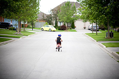 Little boy riding his bicycle on a suburban street, Markham, Ontario - p6071858 by Roderick Chen
