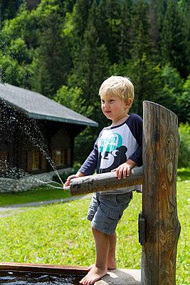 Little boy standing at well - p756m1464828 by Bénédicte Lassalle