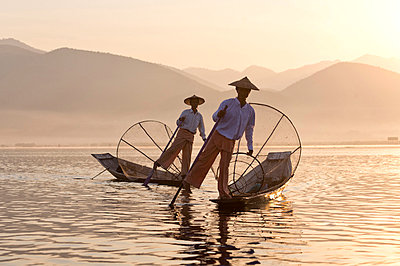 Intha 'leg rowing' fishermen at sunset on Inle Lake who row traditional wooden boats using their leg and fish using nets stretched over conical bamboo frames, Inle Lake - p871m819405 by Lee Frost