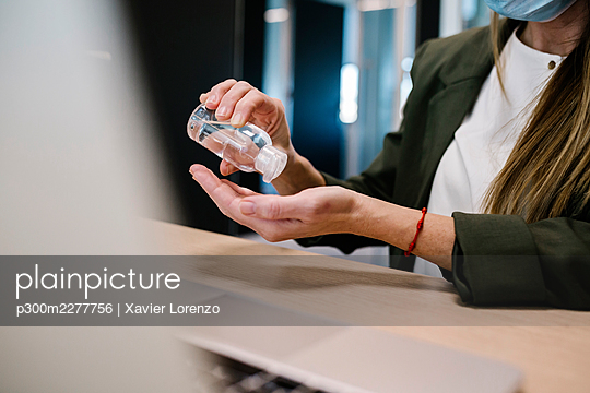 Woman using hand sanitizer at office - p300m2277756 by Xavier Lorenzo