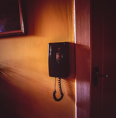Vintage phone with dial plate on the wall - p1082m2205923 by Daniel Allan