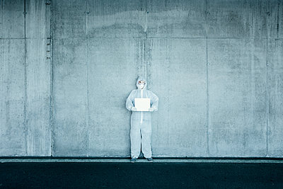 Man wearing protective clothing holding a blank sign - p300m2170901 by Valentin Weinhäupl