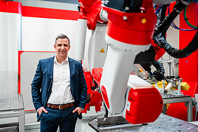 Smiling male entrepreneur with hands in pockets standing at robotics in factory - p300m2265160 by Daniel Ingold