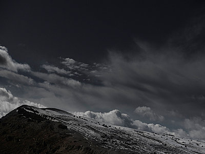 A dramatic cloudy sky above snow covered mountain - p301m844079f by Pep Karsten
