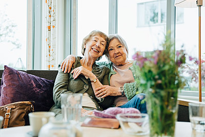 Smiling elderly women sitting with arm around on sofa against window at retirement home - p426m2149331 by Maskot