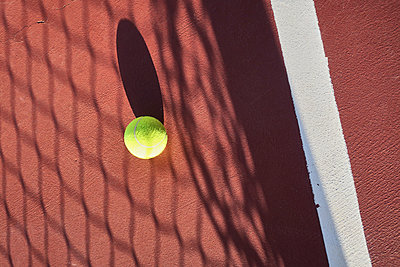 Tennis ball on sand court - p851m1362555 by Lohfink