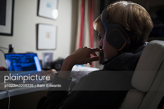 Teenage boy with headphones using computer in dark bedroom - p1023m2208335 by Sam Edwards