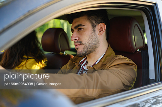 man travelling together on a road trip while driving. Couple of lovers - p1166m2234938 by Cavan Images