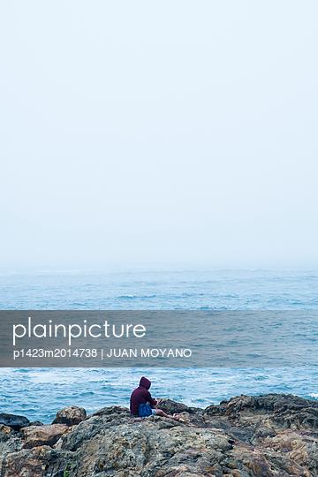 Mann an der Felsküste bei Porto - p1423m2014738 von JUAN MOYANO