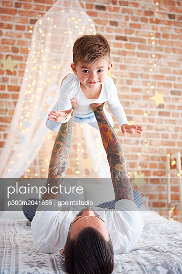 Father lifting up son at Christmas time in bed - p300m2041659 von gpointstudio