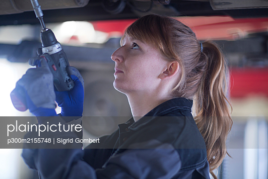 Female car mechanic fixing car standing under bottom in repair garage - p300m2155748 by Sigrid Gombert