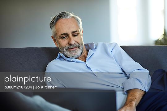 Mature man using laptop on sofa at home - p300m2167204 von Jo Kirchherr