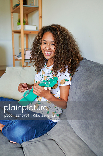 Smiling young afro woman with ukulele sitting on sofa in living room - p300m2243761 by Kiko Jimenez