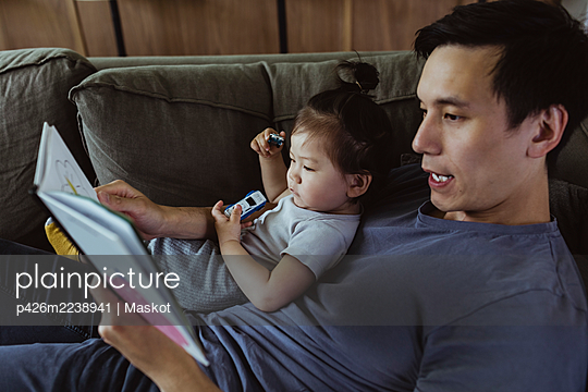 Father with male toddler reading book while lying on sofa in living room - p426m2238941 by Maskot