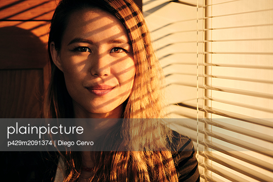 Young woman by window at sunset - p429m2091374 by Diego Cervo