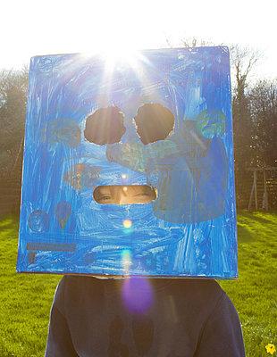 Boy with cardboard box over his head - p1082m1222660 by Daniel Allan