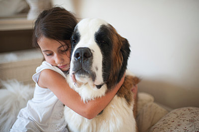 Girl embracing Saint Bernard while sitting on bed at home - p1166m1230477 by Cavan Images