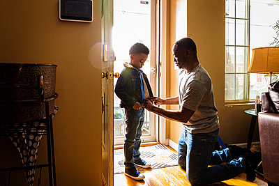 Father helping son in getting dressed at entrance of home - p1166m2279385 by Cavan Images