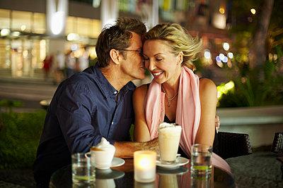 Caucasian man kissing wife in restaurant - p1427m2271521 by Rolf Bruderer