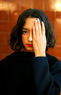 Young woman hand covering eye - p1521m2128957 by Charlotte Zobel