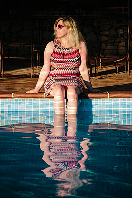 Blond woman sitting at the poolside - p1621m2284067 by Anke Doerschlen