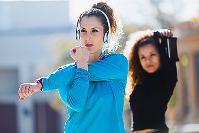 Two focused sportive young women stretching listening to music - p300m1562566 by Josep Suria