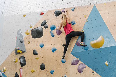 Woman bouldering in climbing gym - p300m2170342 by Hernandez and Sorokina
