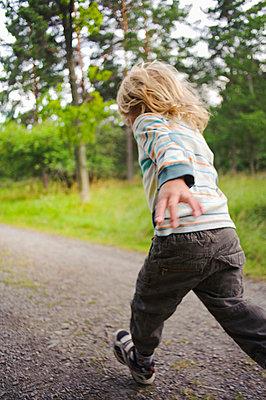 Child running through forest - p312m670304f by Hans Berggren