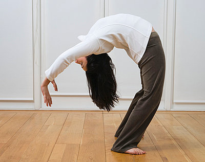 Woman doing back bend - p4292434f by Clarissa Leahy