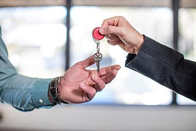 Estate agent handing keys to homebuyer, close-up - p924m1513333 by Zero Creatives