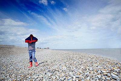 Boy on pebble beach with coat over his head - p924m663850 by Gary John Norman