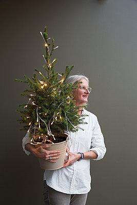 Frau hält kleinen, geschmückten Weihnachtsbaum im Arm. - p948m2014777 von Sibylle Pietrek