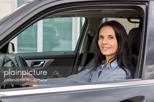 Portrait of smiling woman driving car - p300m2012679 von JLPfeifer