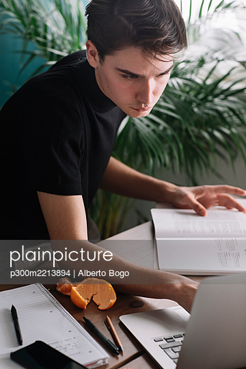 Handsome man using laptop for doing homework at table - p300m2213894 by Alberto Bogo
