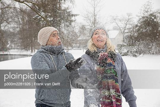Netherlands, Vught. Senior couple having fun in snowy park. - p300m2281926 von Frank van Delft