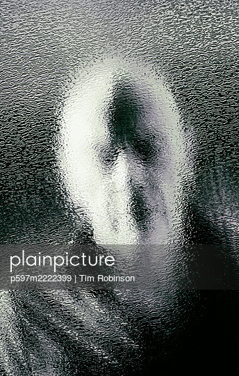Head and shoulders bald man looking through textured glass window - p597m2222399 by Tim Robinson