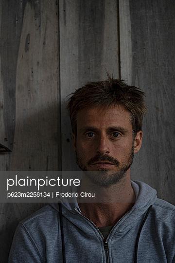 Man sitting in stilt hut - p623m2258134 by Frederic Cirou