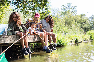 Happy family fishing from sunny riverside dock - p1023m2066690 by Sam Edwards