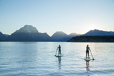 Female friends paddleboarding on lake against clear sky at Grand Teton National Park - p1166m1577832 by Cavan Images