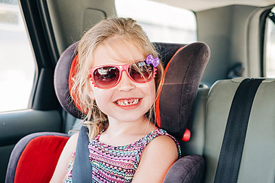 Young girl wearing sunglasses sitting in a car seat - p1166m2208058 by Cavan Images